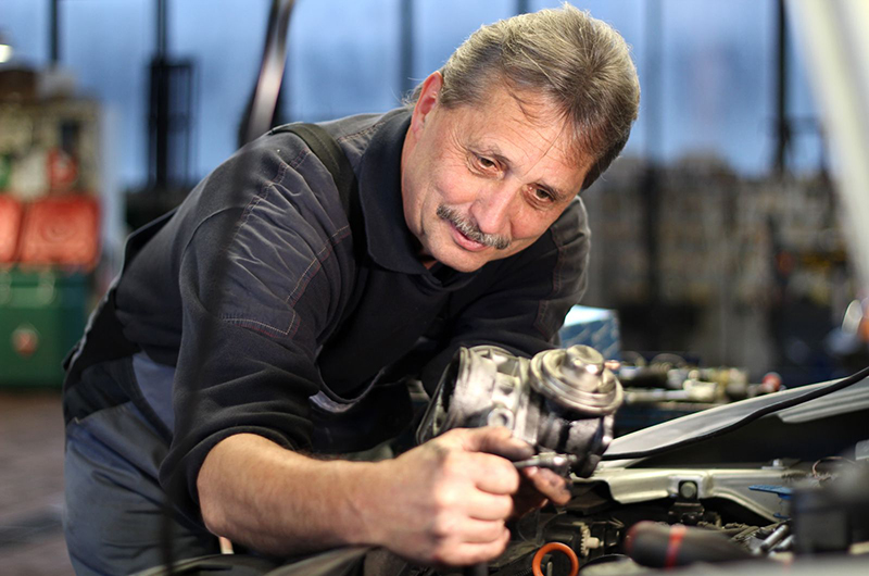 Mitarbeiter repariert Auto | Scheich Car Repair Center